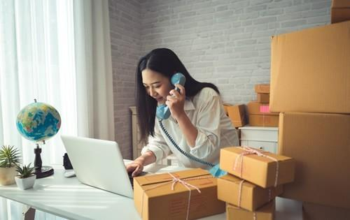 small-business-woman-boxes-on-phone